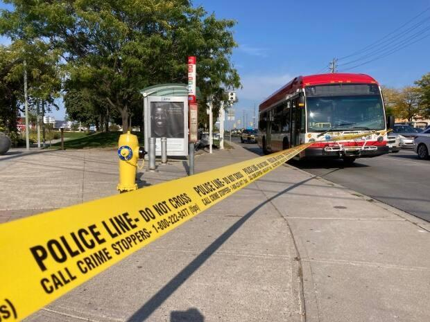 A TTC bus is behind Toronto police tape in this photo after a stabbing happened on the bus on Saturday afternoon. A man was left seriously injured while another man was arrested. (Mark Bochsler/CBC - image credit)