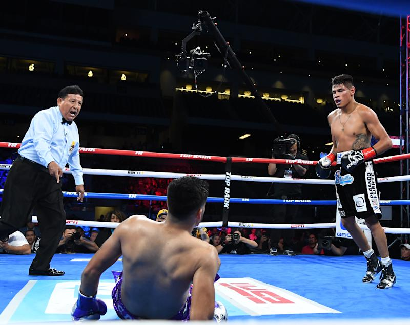 LOS ANGELES, CA - AUGUST 17: Referee Raul Caiz Sr. sends Emanuel Navarrete (black shorts) to a neutral corner after he knocked down Francisco De Vaca (purple shorts) in their WBO World Title fight at Banc of California Stadium on August 17, 2019 in Los Angeles, California. Navarrete won by knockout. (Photo by Jayne Kamin-Oncea/Getty Images)