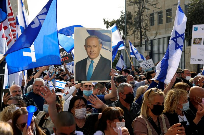 Supporters of Israeli Prime Minister Benjamin Netanyahu, wave flags and hold a placard depicting Netanyahu, during a rally as Netanyahu's corruption trial resumes, near Jerusalem's District Court