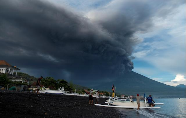 <p>Indonesia's Mount Agung volcano erupts as fishermen pull a boat onto the beach in Amed, Bali, Indonesia, Nov. 26, 2017. (Photo: Petra Simkova/Reuters) </p>