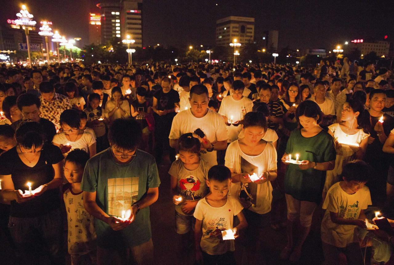 Residents gather as they attend a candlelight vigil for victims of a factory explosion, in Kunshan, Jiangsu province August 2, 2014. China suffered its worst industrial accident in a year on Saturday when an explosion killed at least 68 people and injured more than 120 at a factory in China that makes wheels for U.S. carmakers, including General Motors. REUTERS/Stringer (CHINA - Tags: DISASTER TRANSPORT) CHINA OUT. NO COMMERCIAL OR EDITORIAL SALES IN CHINA