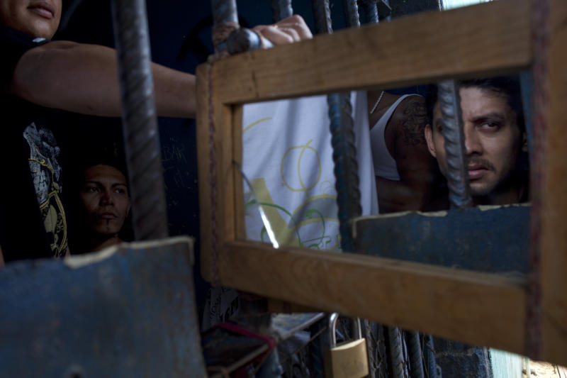 In this May 2, 2012 photo, inmates use a mirror to see outside their cell in San Pedro Sula Central Corrections Facility in San Pedro Sula, Honduras. Inside one of Honduras' most dangerous and overcrowded prisons, inmates operate a free-market bazaar, selling everything from iPhones to prostitutes. Guards do not cross into the inner sanctum controlled by prisoners, and prisoners do not breach the perimeter controlled by guards. (AP Photo/Rodrigo Abd)