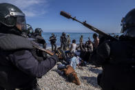 Migrants are surrounded by Spanish police near the border of Morocco and Spain, at the Spanish enclave of Ceuta, on Tuesday, May 18, 2021. (AP Photo/Bernat Armangue)