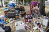 """Dawn Woodward, 39, who is homeless and originally from Arizona, sits outdoors in a homeless camp on the side of the CA-101 highway in Echo Park neighborhood in Los Angeles Tuesday, May 11, 2021. California Gov. Gavin Newsom on Tuesday proposed $12 billion in new funding to get more people experiencing homelessness in the state into housing and to """"functionally end family homelessness"""" within five years. (AP Photo/Damian Dovarganes)"""
