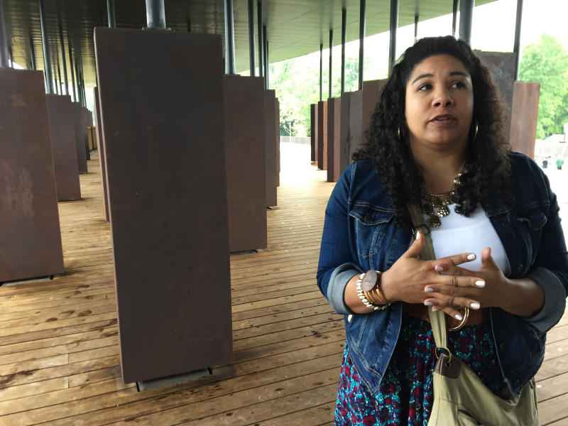"""Angel Smith Dixon stands inside a display at the National Memorial for Peace and Justice, a new memorial to honor people killed in racist lynchings, which opened to the public Thursday, April 26, 2018, in Montgomery, Ala. Smith Dixon who came from Lawrenceville, Ga., to see the memorial said, """"We're publicly grieving this atrocity for the first time as a nation. ... You can't grieve something you can't see, something you don't acknowledge. Part of the healing process, the first step is to acknowledge it."""" (AP Photo/Beth J. Harpaz)"""
