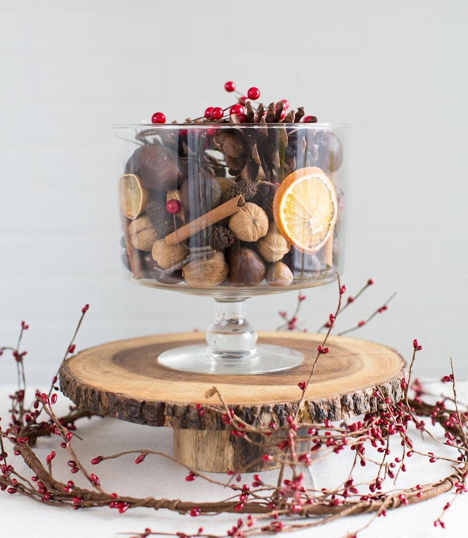 """<p>This <a href=""""https://www.goodhousekeeping.com/holidays/christmas-ideas/how-to/g1608/quick-christmas-centerpieces/"""" rel=""""nofollow noopener"""" target=""""_blank"""" data-ylk=""""slk:five-minute centerpiece"""" class=""""link rapid-noclick-resp"""">five-minute centerpiece</a> is as easy as filling a glass container with unshelled nuts, faux cranberries, pine cones, cinnamon sticks, and dried citrus. Centered on a polished wood slice, the table's good to go.</p><p><a class=""""link rapid-noclick-resp"""" href=""""https://www.amazon.com/Anchor-Hocking-Monaco-Trifle-Bowl/dp/B0002YSLXC/?tag=syn-yahoo-20&ascsubtag=%5Bartid%7C10055.g.2196%5Bsrc%7Cyahoo-us"""" rel=""""nofollow noopener"""" target=""""_blank"""" data-ylk=""""slk:SHOP TRIFLE BOWLS"""">SHOP TRIFLE BOWLS</a></p>"""