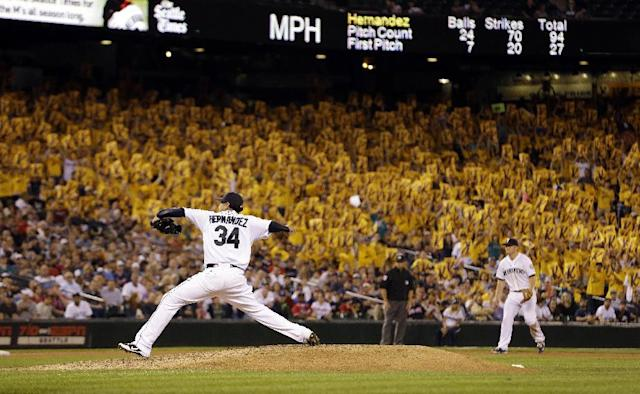 """A sea of yellow """"K"""" cards, designating a strikeout, are held in the stands behind Seattle Mariners staring pitcher Felix Hernandez as he throws against the Atlanta Braves in the eighth inning of a baseball game Tuesday, Aug. 5, 2014, in Seattle. (AP Photo/Elaine Thompson)"""