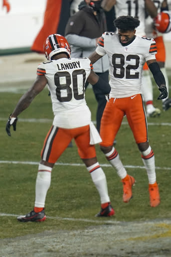 Cleveland Browns wide receivers Jarvis Landry (80) and Rashard Higgins (82) celebrate after defeating the Pittsburgh Steelers in an NFL wild-card playoff football game, late Sunday, Jan. 10, 2021, in Pittsburgh. (AP Photo/Keith Srakocic)