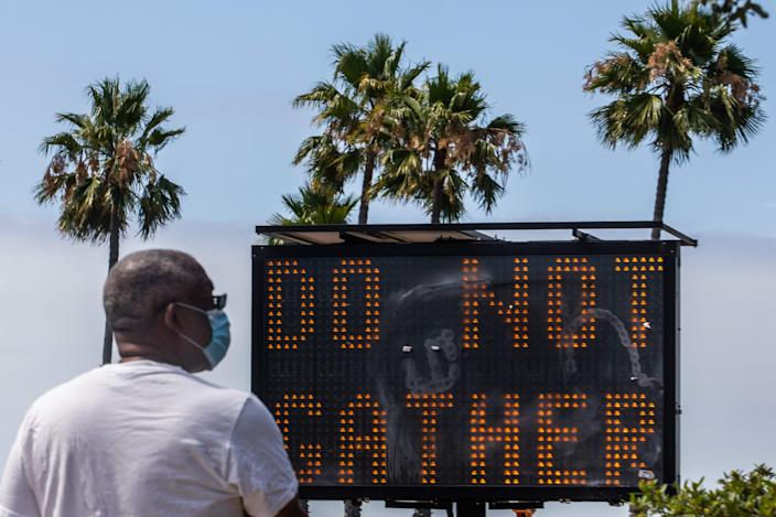 A man wearing a facemask checks his phone near a sign urging people not to gather, while he walks on the beach in Long Beach, Calif. on July 14, 2020. California's Governor Gavin Newsom announced a significant rollback of the state's reopening plan on July 13, 2020 as coronavirus cases soared across America's richest and most populous state.