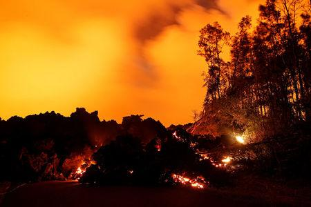 A lava flow from the Kilauea volcano illuminates the night sky in the Leilani Estates near Pahoa Hawaii U.S