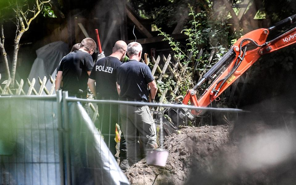 Police watch on as the digger excavates the plot - AP