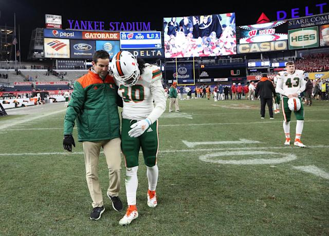 Miami defensive coordinator Manny Diaz consoles Miami defensive back Romeo Finley (30) walking off the field after a 35-3 loss against Wisconsin. (Getty Images)