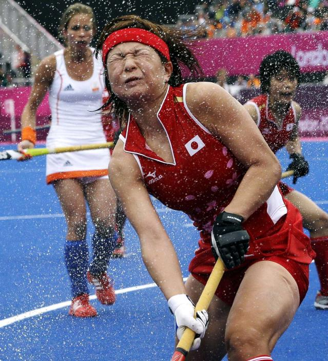 Japan's Nagisa Hayashi grimaces as water sprays in her face during a match against the Netherlands during a women's preliminary field hockey match at the 2012 Summer Olympics, Tuesday, July 31, 2012, in London. The Netherlands won 3-2. (AP Photo/Bullit Marquez)