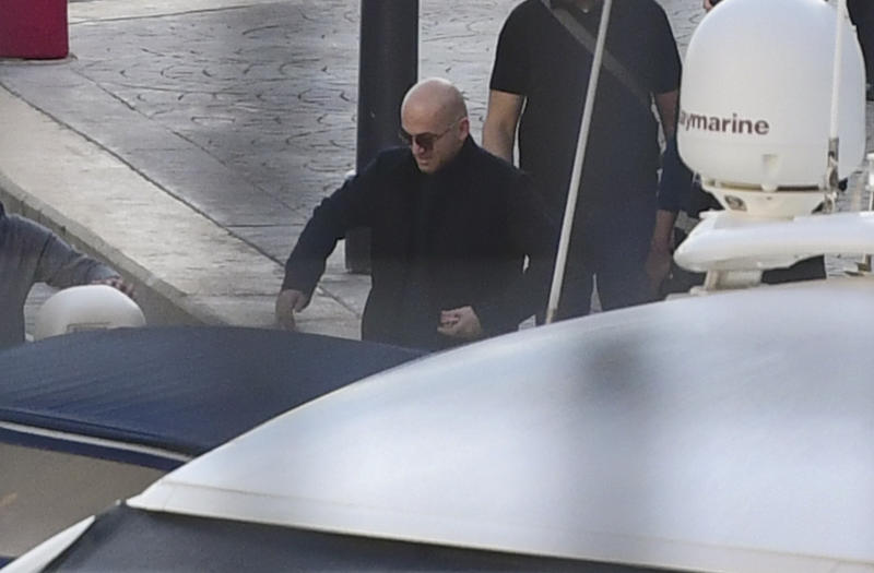 Maltese businessman Yorgen Fenech is accompanied by police during a search of his yacht at the dock of Portomaso, Malta, Friday, Nov. 22, 2019. Fenech was arrested Wednesday, then released on police bail late Thursday as investigators try to find a mastermind of the 2017 murder of investigative reporter Daphne Caruana Galizia on the small island nation. (AP Photo/stringer)