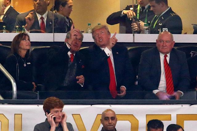 President Donald Trump takes in the college football national championship while chatting with Atlanta Falcons owner Arthur Blank (L) in January. (Getty Images)