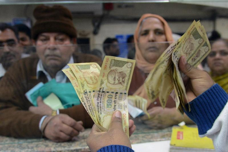 An Indian bank teller counts out notes as senior citizens gather inside a bank to exchange 500 and 1000 rupee notes in Amritsar on November 19, 2016 (AFP Photo/Narinder Nanu)