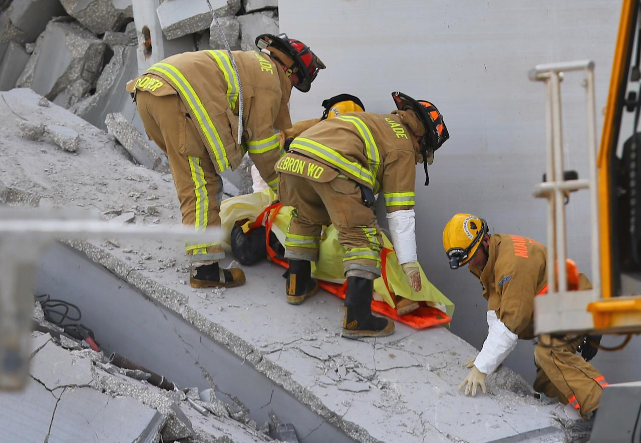 MIAMI, FL - OCTOBER 10:  Miami-Dade Rescue workers pull a body out of the rubble of a four-story parking garage that was under construction and collapsed at the Miami Dade College's West Campus on October 10, 2012 in Doral, Florida.  Early reports indicate that one person was killed, at least seven people injured and an unknown number of people may be buried in the rubble.  (Photo by Joe Raedle/Getty Images)