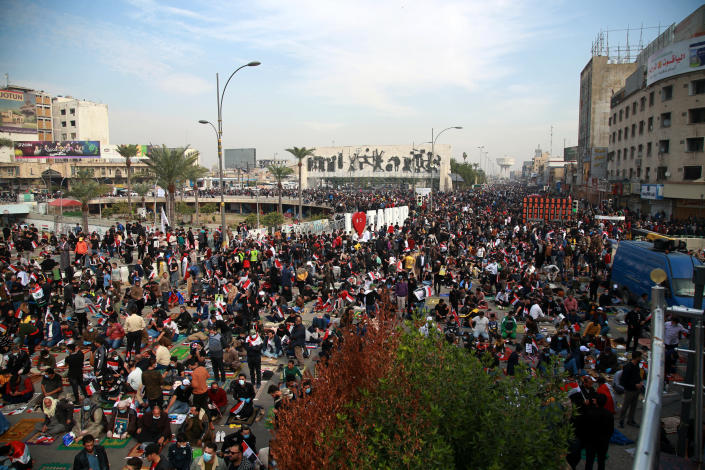 Followers of Shiite cleric Muqtada al-Sadr,gather in Tahrir Square, Baghdad, Iraq, Friday, Nov. 27, 2020. Thousands took to the streets in Baghdad on Friday in a show of support for a radical Iraqi cleric ahead of elections slated for next year, stirring fears of a spike in coronavirus cases. (AP Photo/Khalid Mohammed)