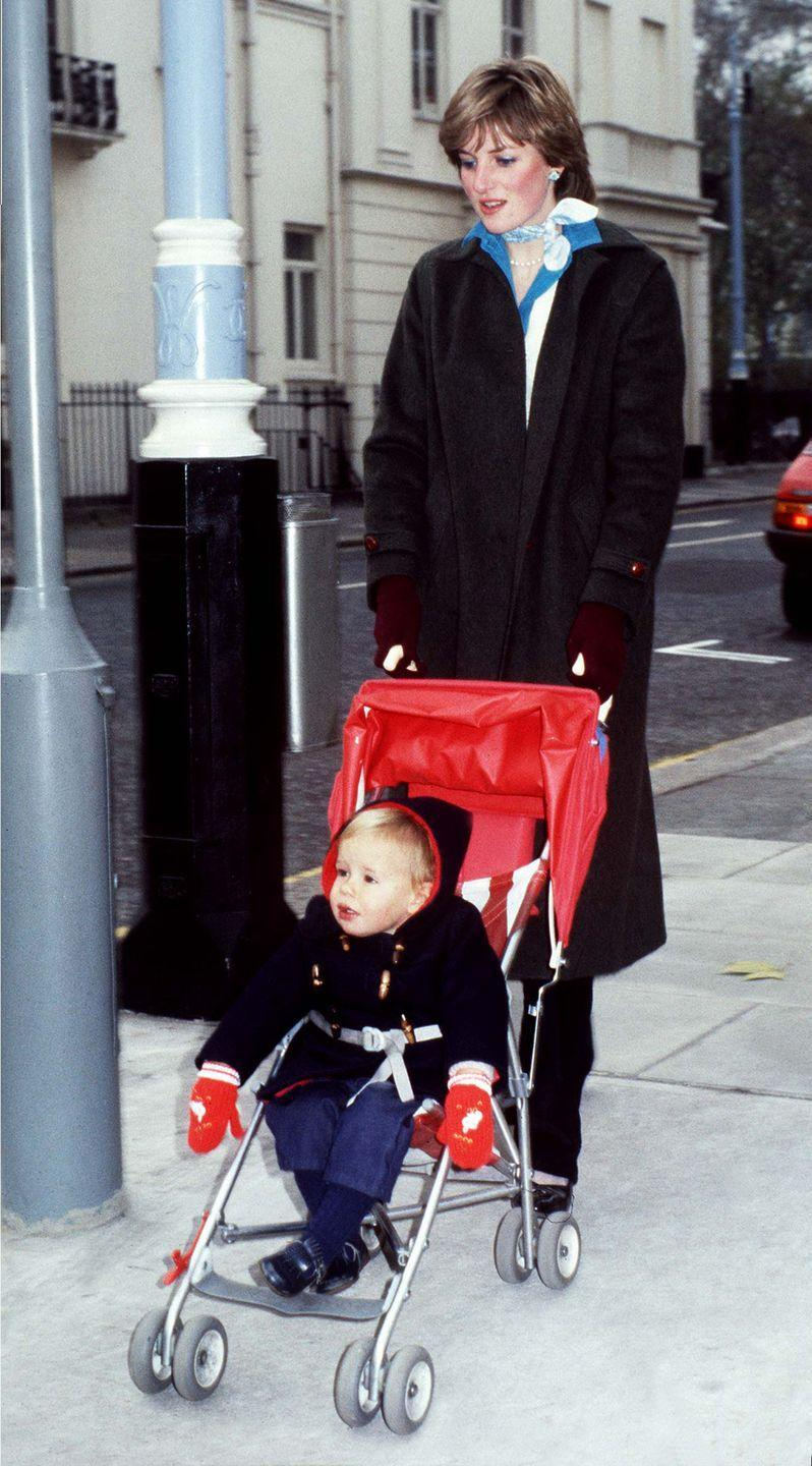 <p>In a blue shirt, black trousers, and gray coat, accessorized with red gloves, stud earrings, and printed scarf in the Eaton Square district of London. </p>