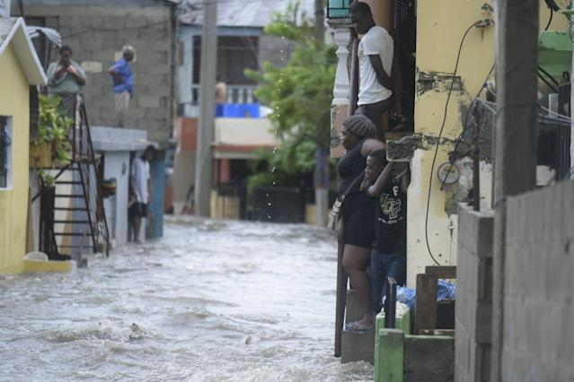 <p>People watch flooded water in a street in Santiago de los Caballeros, Dominican Republic, Sept. 7, 2017. (Photo: Luis Tavarez/EPA-EFE/REX/Shutterstock) </p>