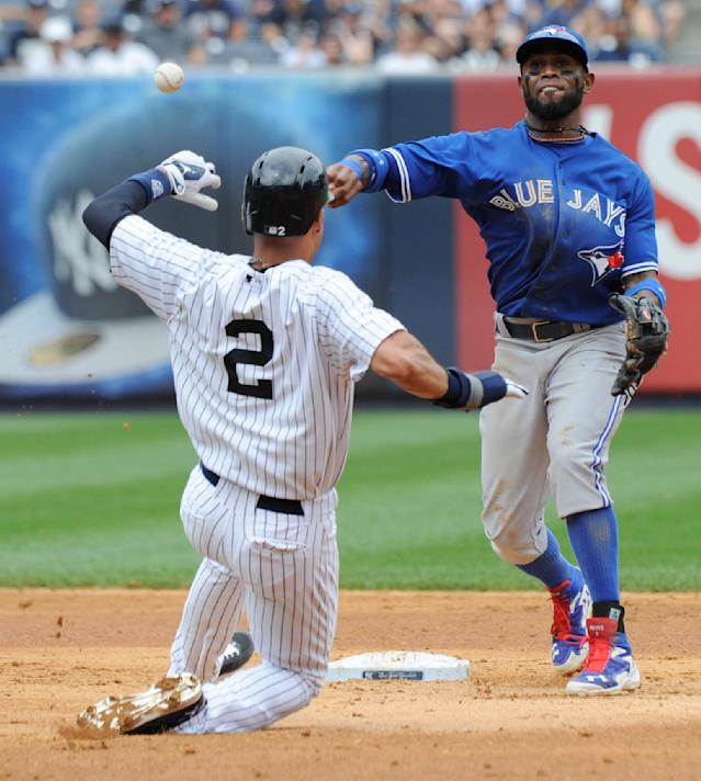 New York Yankees' Derek Jeter is out at second as Toronto Blue Jays shortstop Jose Reyes, right, throws to first attempting to get Jacoby Ellsbury at first during the fifth inning of a baseball game Saturday, July 26, 2014, at Yankee Stadium in New York. Ellsbury was safe at first. (AP Photo/Bill Kostroun)