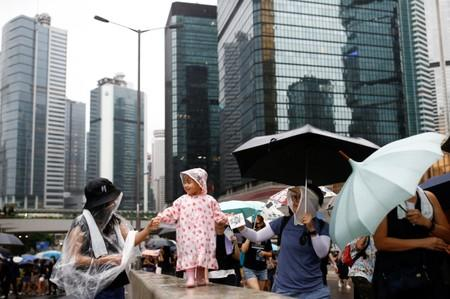 Anti-extradition bill protesters lead a child as they attend a rally in Hong Kong