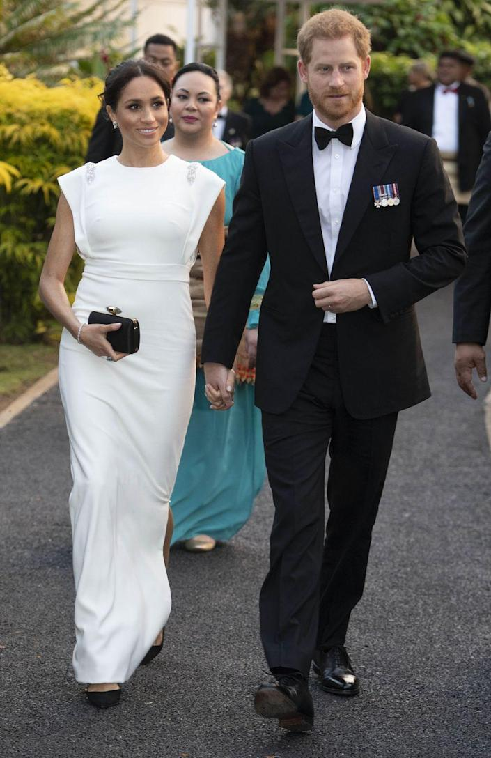 """<p>On a royal visit to Tonga, the Duchess of Sussex wore a white sheath gown designed by Theia. She added diamond earrings and <a href=""""https://www.harpersbazaar.com/celebrity/latest/a24210265/meghan-markle-royal-tour-white-theia-evening-gown-dress-tonga/"""" rel=""""nofollow noopener"""" target=""""_blank"""" data-ylk=""""slk:Princess Diana's aquamarine cocktail ring"""" class=""""link rapid-noclick-resp"""">Princess Diana's aquamarine cocktail ring</a> to the cap-sleeved evening gown. </p>"""