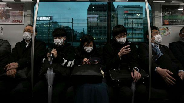 PHOTO: Commuters wearing masks sit on a train in Tokyo, March 2, 2020. (Jae C. Hong/AP)