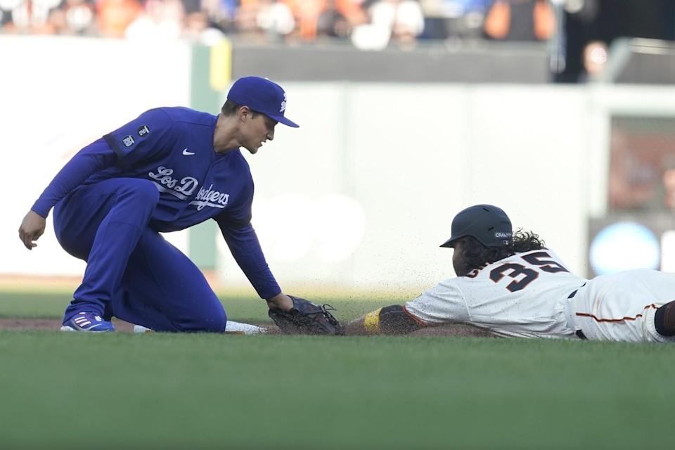A Dodgers player tags a Giants player sliding head first