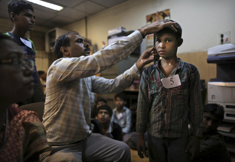 A young Indian bonded child laborer's height is measured as he is processed at the district magistrates office after being rescued during a raid by workers from Bachpan Bachao Andolan or Save the Childhood Movement, at a garment factory in New Delhi, India, Tuesday, June 12, 2012. Police raids on factories in the Indian capital revealed dozens of migrant kids hard at work Tuesday despite laws against child labor. Police rounded up 26 children from three textiles factories and a metal processing plant, but dozens more are believed to have escaped. Those captured had all come to New Delhi from the states of Bihar and Uttar Pradesh. (AP Photo/Kevin Frayer)
