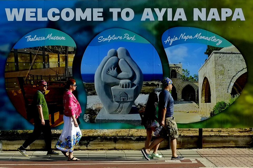 Tourist walk at southeast resort of Ayia Napa, in the eastern Mediterranean island of Cyprus, Saturday, May 22, 2021. Cypriot hotel and other tourism-related business owners say they'd like to see the COVID-19 pandemic-induced uncertainty over travel bookings to the tourism-reliant island nation winding down by July when they're hoping authorities in Cyprus' main markets including the U.K., Russia, Germany and the Scandinavian countries will make it easier for their citizens to travel abroad. (AP Photo/Petros Karadjias)