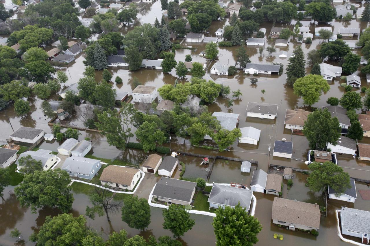 In this aerial photo the flood waters of the Souris River flow through a neighborhood Friday, June 24, 2011 in Minot, N.D. The Souris River set a ecord for flooding, rising so quickly that it could be seen climbing up the side of homes in the North Dakota city. (AP Photo/Charles Rex Arbogast)