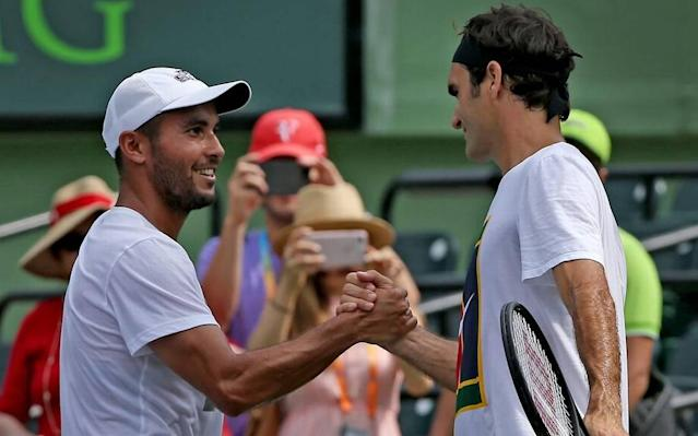 Roger Federer shakes hands with his hitting partner Adrian Escarate (L) prior to the men's final at the Miami Open between Roger Federer and Rafael Nadal at the Crandon Park Tennis Center on April 2, 2017. Escarate is a DACA recipient who says tennis is his greatest passion and he hopes to become a sports commentator (Patrick Farrell/Miami Herald)