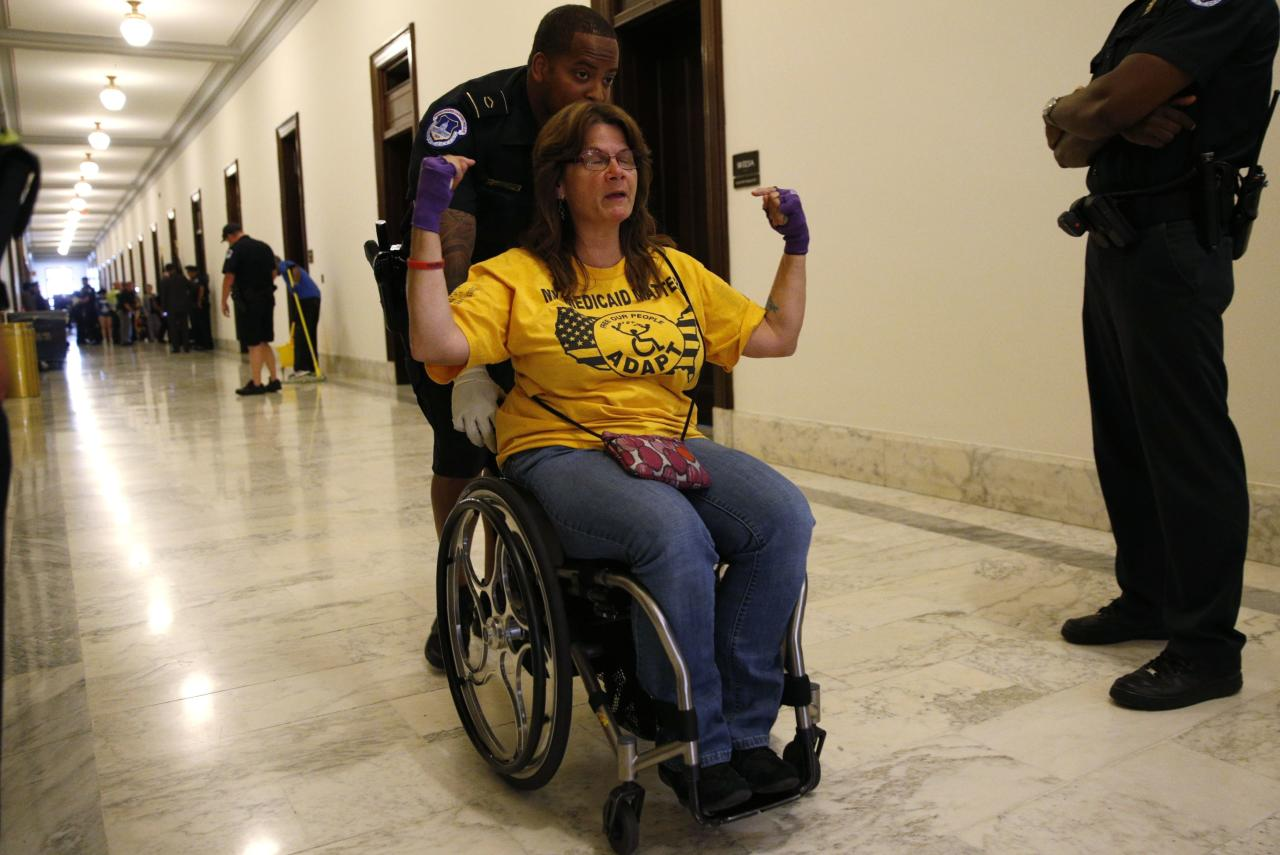 """A protester calling for """"no cuts to Medicaid"""" is escorted away by police after being arrested during a demonstration outside Senate Majority Leader Mitch McConnell's constituent office after Senate Republicans unveiled their healthcare bill on Capitol Hill in Washington, U.S., June 22, 2017. REUTERS/Kevin Lamarque"""