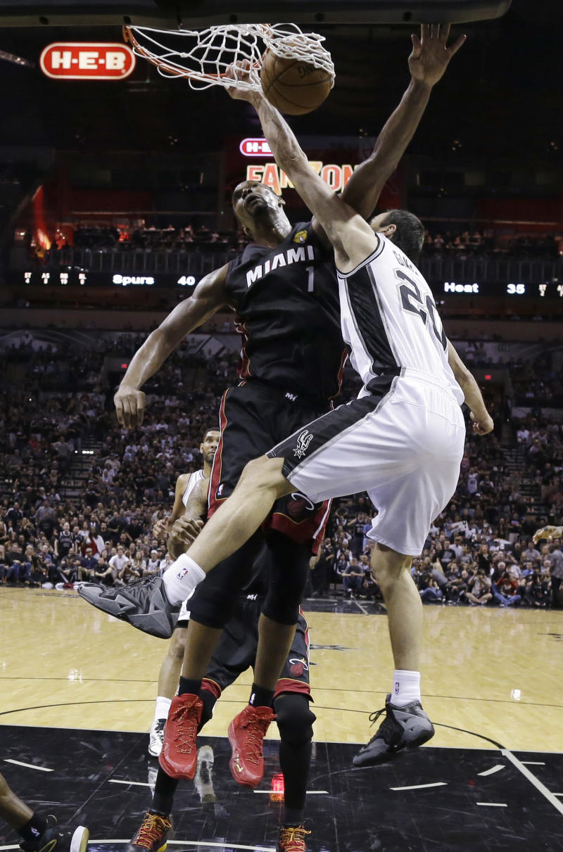 San Antonio Spurs guard Manu Ginobili (20) dunks over Miami Heat center Chris Bosh (1) during the first half in Game 5 of the NBA basketball finals on Sunday, June 15, 2014, in San Antonio