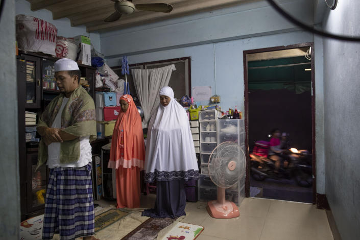 A Muslim family pray after breaking fast at the living room of their house as a food-delivery man rides past in Bangkok, Thailand, April 28, 2020. (AP Photo/Gemunu Amarasinghe)