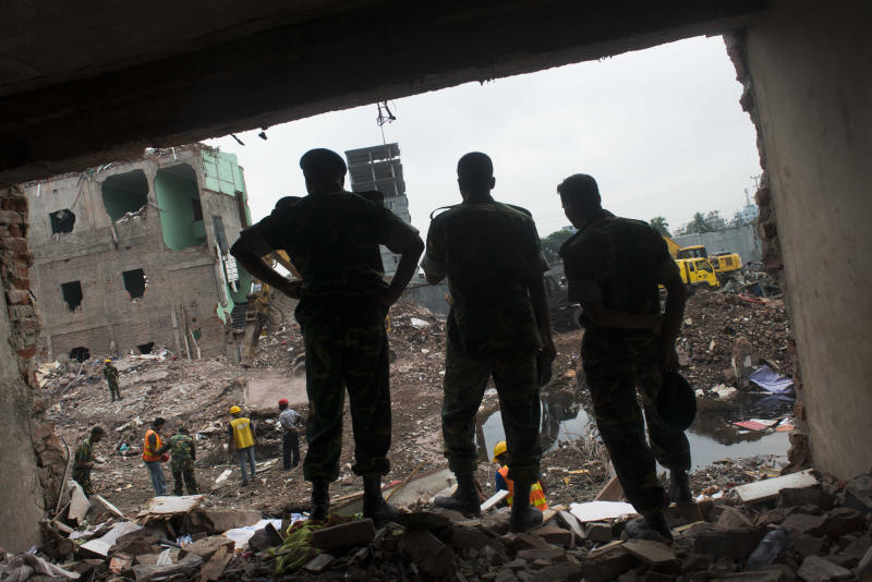 FILE - In this Sunday, May 12, 2013 file photo, Bangladeshi soldiers stand amid the rubble of the garment factory building that collapsed on April 24 as they continue search operation in Savar, near Dhaka, Bangladesh. A government investigation said poor quality construction materials and building code violations contributed to the collapse of building housing garment factories last month in Bangladesh. (AP Photo/Ismail Ferdous, File)