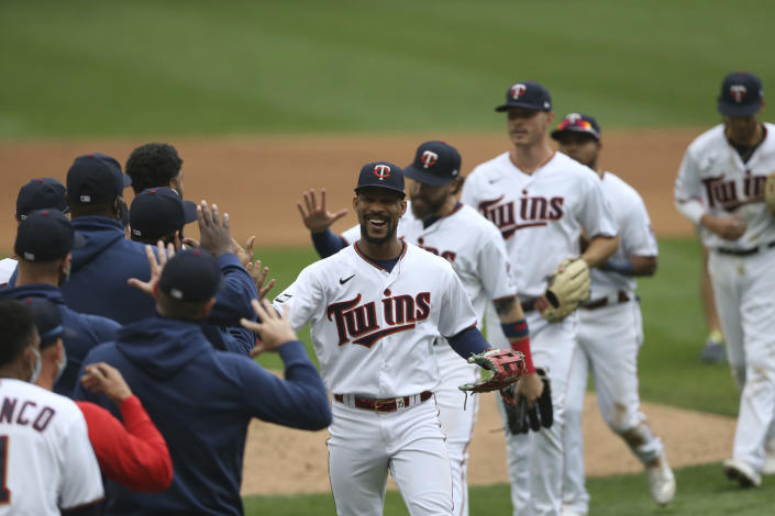 Minnesota Twins' Byron Buxton, center, smiles as he high-fives teammates after defeating the Kansas City Royals in a baseball game Sunday, May 2, 2021 in Minneapolis. (AP Photo/Stacy Bengs)