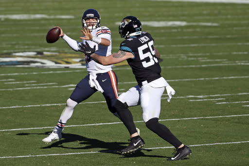 Chicago Bears quarterback Mitchell Trubisky, left, looks for a receiver as Jacksonville Jaguars defensive end Aaron Lynch (59) tries to stop him during the first half of an NFL football game, Sunday, Dec. 27, 2020, in Jacksonville, Fla. (AP Photo/Stephen B. Morton)
