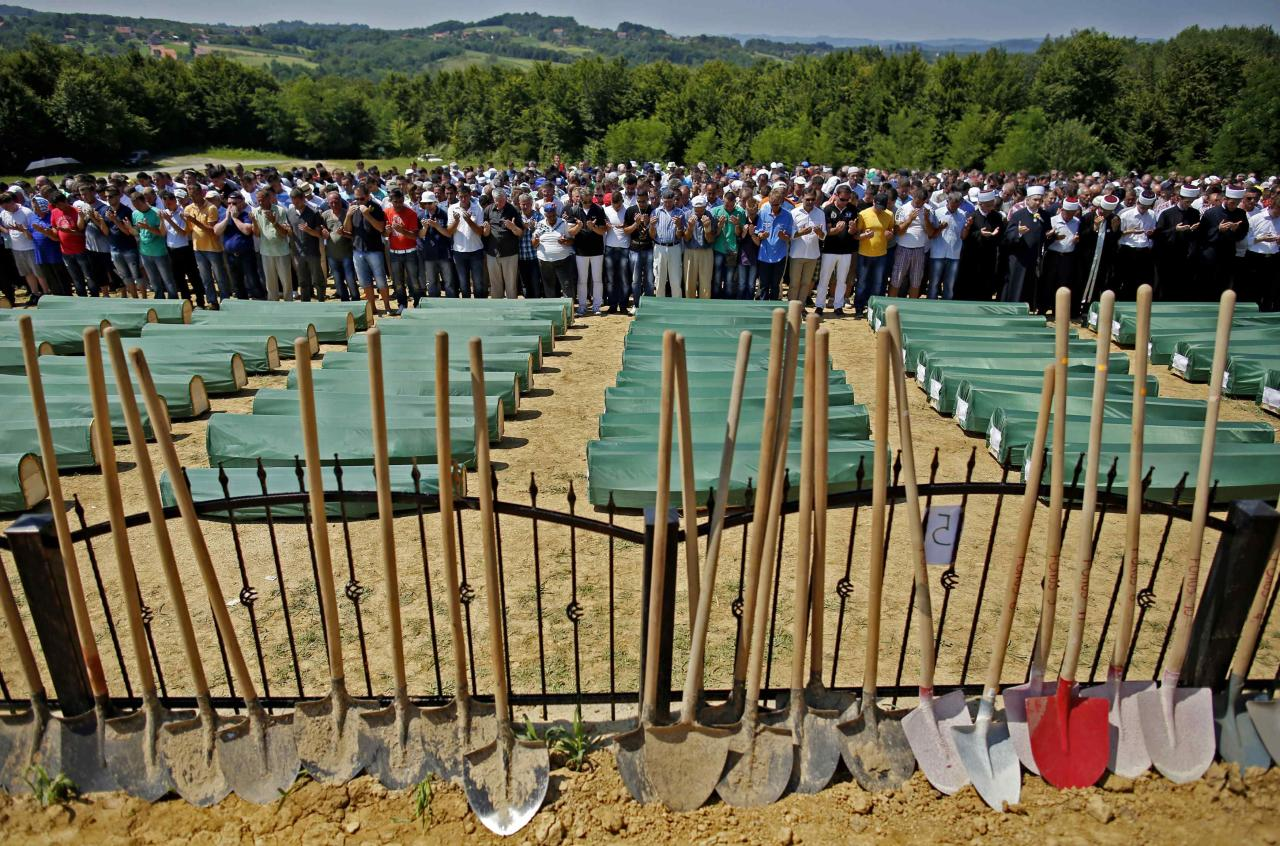 Bosnian Muslims pray in front of coffins of their relatives during a mass funeral in the village of Biscani, near Prijedor, July 20, 2014. Seventy seven Muslims were killed in Biscani village in the war. The collective burial of 284 Bosnian Muslims and Croats, whose remains were found and identified in a northwestern mass grave and believed to be the largest from Bosnia's 1992-95 war, will take place on Sunday. REUTERS/Dado Ruvic (BOSNIA AND HERZEGOVINA - Tags: POLITICS CIVIL UNREST CONFLICT RELIGION TPX IMAGES OF THE DAY)