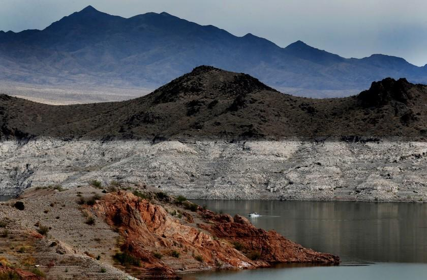 """LAKE MEAD, NEV. - JUNE 11, 2021. A boat navigates Lake Mead, where a white """"bathtub ring"""" along the shore shows how far below capacity the nation's largest reservoir currently is. Water levels at Lake Mead have hit their lowest points in history amid an ongoing megadrought, creating uncertainty about the water supply for millions of people in the western United States. (Luis Sinco / Los Angeles Times)"""