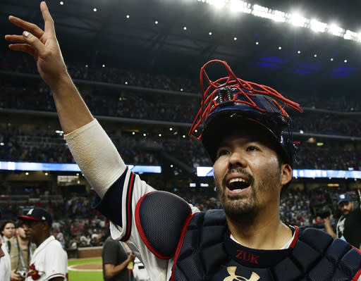 FILE - In this Oct. 7, 2018, file photo, Atlanta Braves catcher Kurt Suzuki celebrates after Game 3 of baseball's National League Division Series against the Los Angeles Dodgers, in Atlanta. Catcher Kurt Suzuki is heading back to the Washington Nationals after agreeing to a $10 million, two-year contract, a deal pending a successful physical. The deal was disclosed to The Associated Press on Monday, Nov. 19, 2018, by a person familiar with the agreement who spoke on condition of anonymity because the contract was not yet official. (AP Photo/John Amis, File)