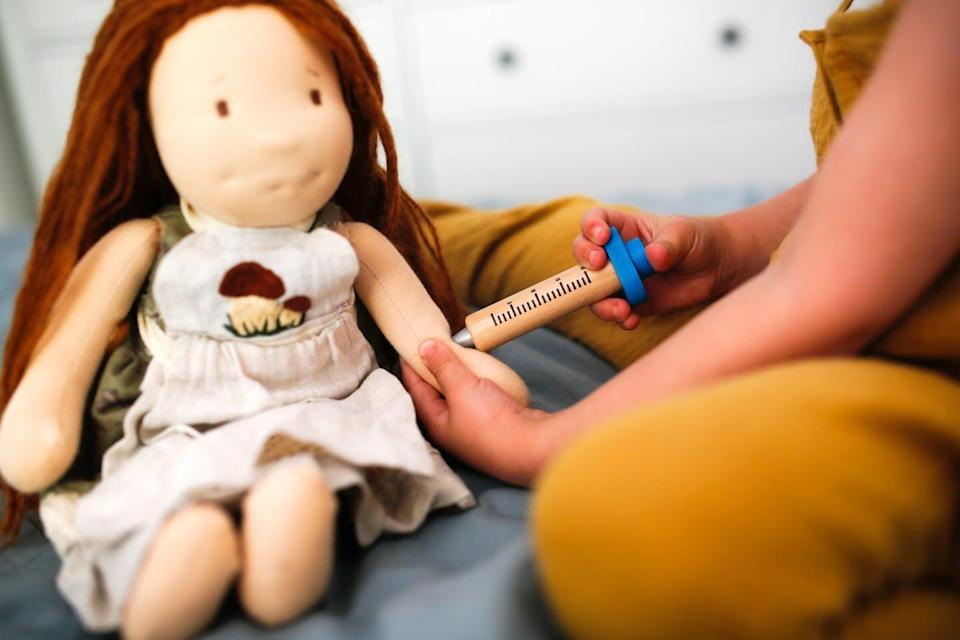A child gives a doll a vaccine.