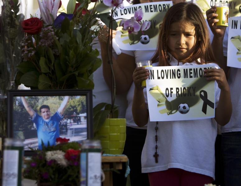 Friends and family hold signs and candles during a news conference to talk about the death of Ricardo Portillo, who passed away after injuries he sustained after an assault by a soccer player at a soccer game he was refereeing on April 27, in Salt Lake City on Sunday, May 5, 2013. (AP Photo/The Salt Lake Tribune, Kim Raff)