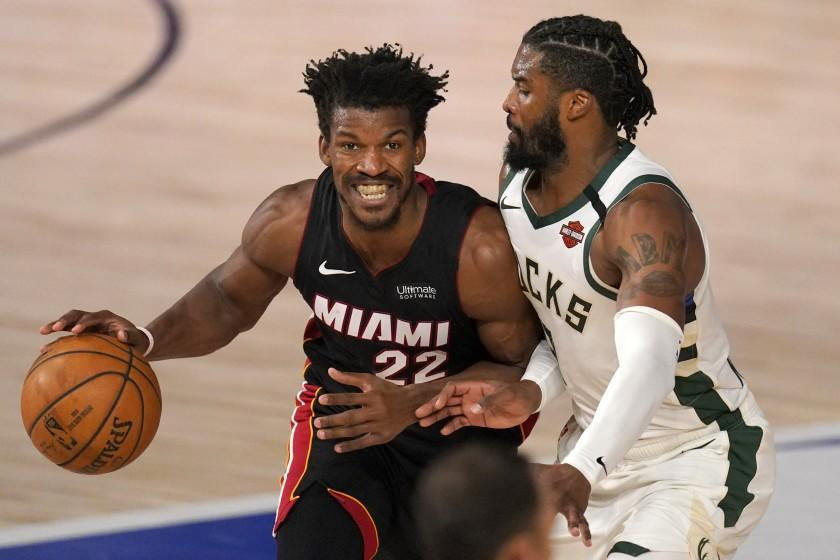 Miami Heat's Jimmy Butler (22) works to move the ball up court as Milwaukee Bucks' Wesley Matthews, right, defends during the first half of an NBA basketball conference semifinal playoff game, Monday, Aug. 31, 2020, in Lake Buena Vista, Fla. (AP Photo/Mark J. Terrill)