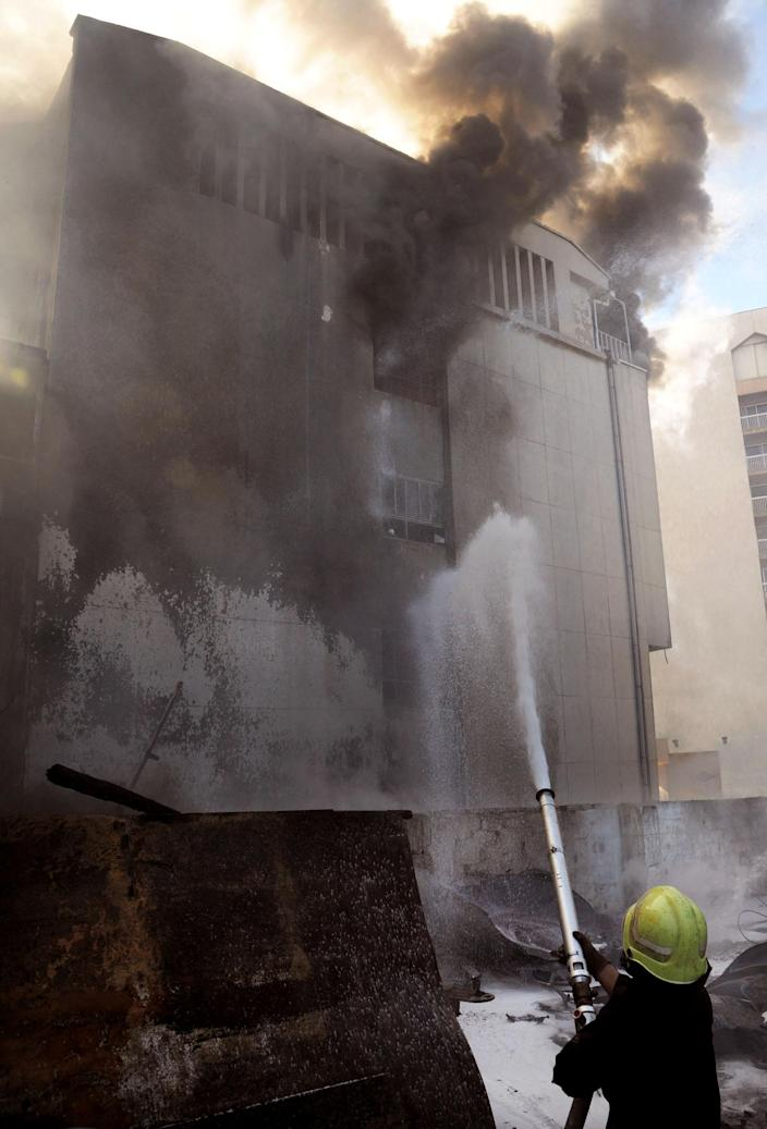 In this photo released by the Syrian official news agency SANA, a firefighter extinguishes a building after a bomb attached to a fuel truck exploded outside a Damascus hotel where U.N. observers are staying according to the Syria's state TV in Damascus, Syria, on Wednesday Aug. 15, 2012. According to an Associated Press reporter at the scene, the blast had gone off inside a different parking lot, one belonging to a military compound and not the military command. The lot is near the Dama Rose Hotel, popular with the U.N. observers in Syria. (AP Photo/SANA)