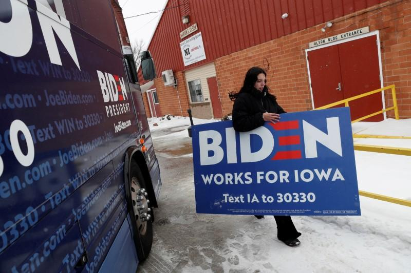FILE PHOTO: A campaign worker for Democratic 2020 U.S. presidential candidate and former U.S. Vice President Joe Biden carries a sign after a campaign event in Mason City, Iowa