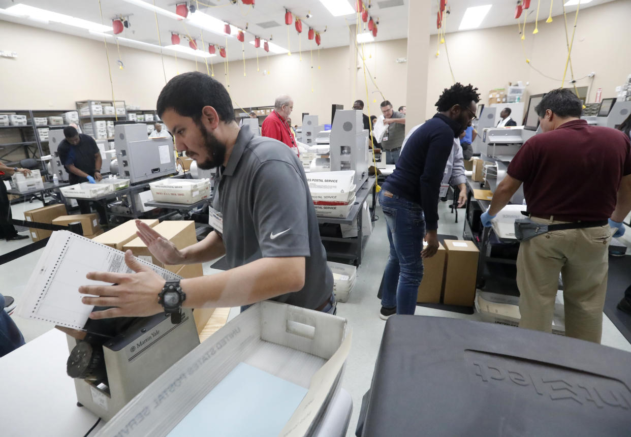 Employees at the Broward County elections office recount ballots Wednesday in Lauderhill, Fla. (Photo: Wilfredo Lee/AP)