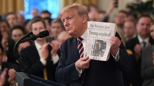 PHOTO: President Donald Trump holds up a newspaper that displays a headline 'Acquitted' while peaking about his Senate impeachment trial in the East Room of the White House, Feb. 6, 2020. (Saul Loeb/AFP via Getty Images)