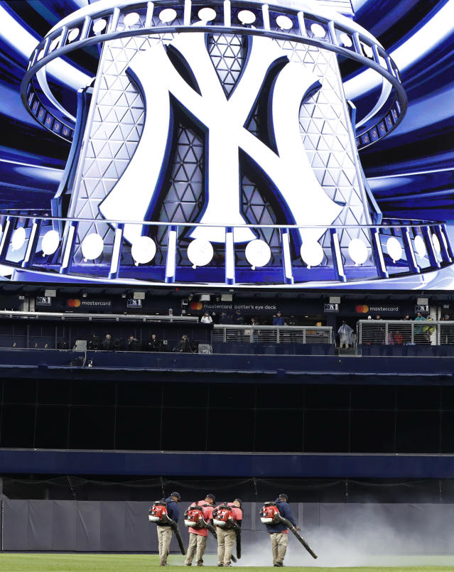 Groundskeepers use leaf blowers to remove water from center field at Yankee Stadium before a baseball game between the New York Yankees and the Baltimore Orioles, Monday, May 13, 2019, in New York. The game was postponed until Wednesday afternoon due to unplayable field conditions. (AP Photo/Kathy Willens)